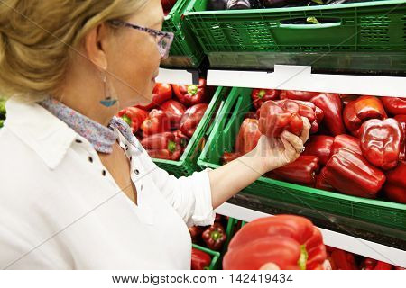 Portrait Of Attractive Female Pensioner Shopping For Fruits And Vegetables In Produce Department Of