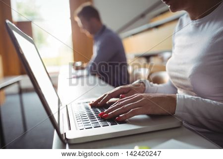Mid section mature student using laptop in the classroom