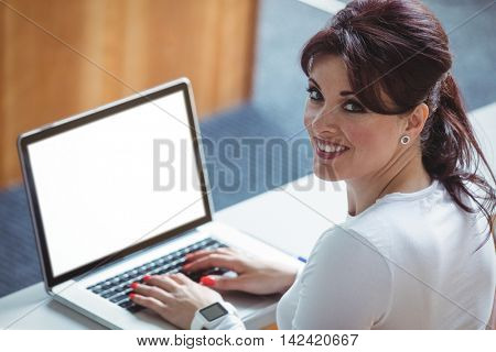 Portrait of mature student using laptop in the classroom