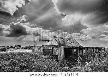Black and white photograph of a derelict farm in Suffolk with billowing clouds