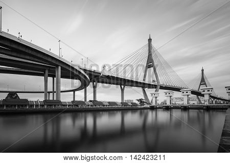 Black and White, Twin suspension bridge over watergate with moving clouds background