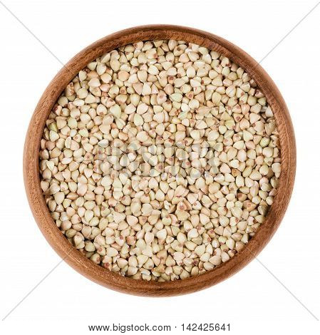 Buckwheat in a wooden bowl on white background. Small grain seeds of Fagopyrum esculentum. Edible, raw and organic food. Isolated close up macro photo.
