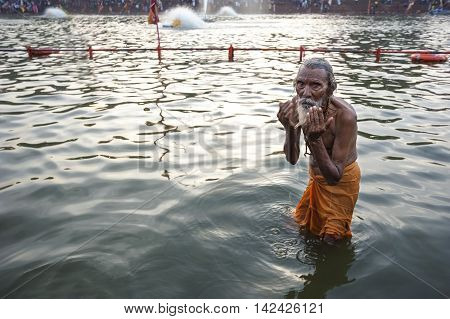 Ujjain Madhya Pradesh India - May 18 2016: An old man bathes in the Kshipra River during the Kumbh Mela religious festival in Ujjain India on May 18 2016. The Kumbh Mela is the largest event on Earth which attracts millions of Hindu worshippers over the c