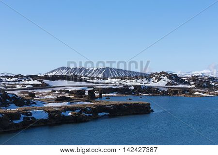 Myvatn volcano mount and blue lake, Winter landscape, Iceland with clear blue sky background