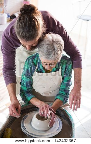 Male potter assisting female potter while making pot in pottery workshop