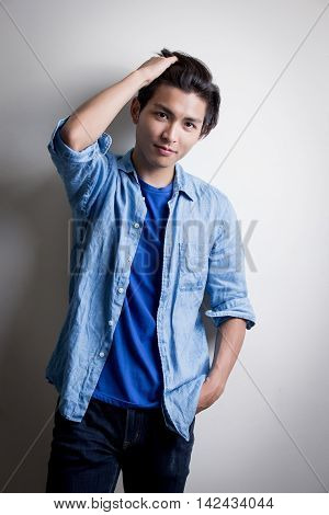 handsome man wear denim shirt and look seriousisolated white backgroundasian