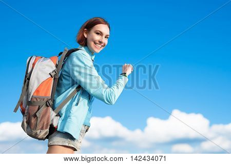 happy woman mountain hiker go to travel and look smart watch with blue sky and white clouds caucasian