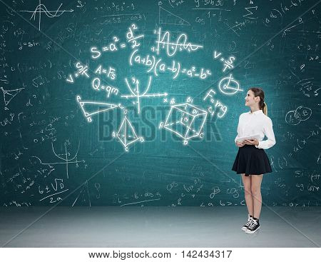 Woman with tablet standing near blue green chalkboard looking at complex formulas. Concept of exact sciences
