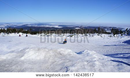Sledding hill at Fichtelberg in the Ore Mountains, Germany, snowy winter landscape and view on the mountain peaks Pohlberg and Bärenstein