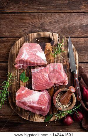 raw pork meat on dark wooden board top view
