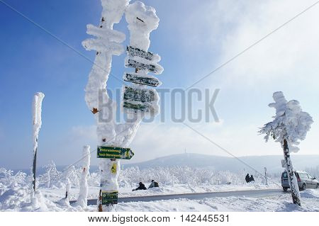 Hikers on the Fichtelberg in the Erzgebirge, Germany, view to the Klinovec in Czech Republic, thick snowy signposts and spruces, blue sky and clouds