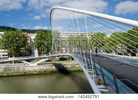 BILBAO, SPAIN. 28th July 2016. People crossing the Zubizuri. Bilbao's famous white bridge was designed by Santiago Calatrava, and was the subject of an almost equally famous lawsuit.