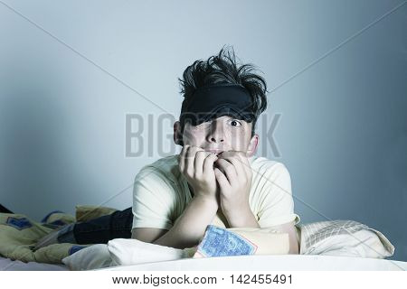 scared and sleepless boy chewing fingernails at bedroom