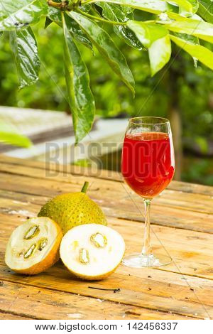 Green baby jackfruit and juice on wooden background.fruit for health and stillife.