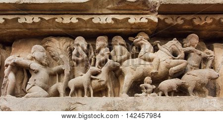 Village and rural people with animals on stone relief of Khajuraho temple India. UNESCO Heritage site built between 950 and 1150 in India belong to Hinduism and Jainism.