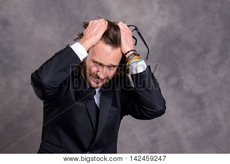 Stressed Young Businessman In Black Suit