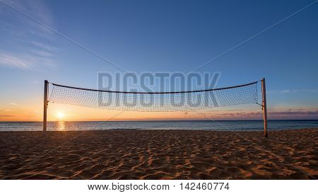 Sillhouette of a volleyball net against sunrise on the beach