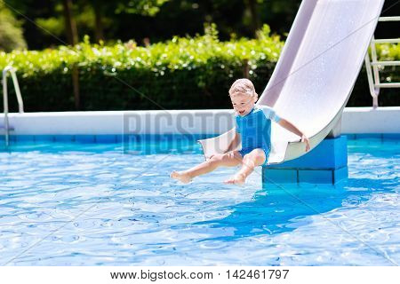Happy laughing little boy playing on water slide in outdoor swimming pool on a hot summer day. Kids learn to swim. Child wearing sun protection rash guard sliding on aqua playground in tropical resort