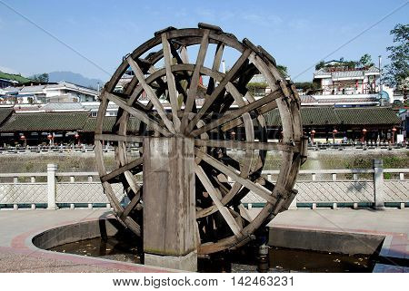 Dujiangyan China - November 1 2007: Miniature wooden water wheel on the quaiy running net to the Min River