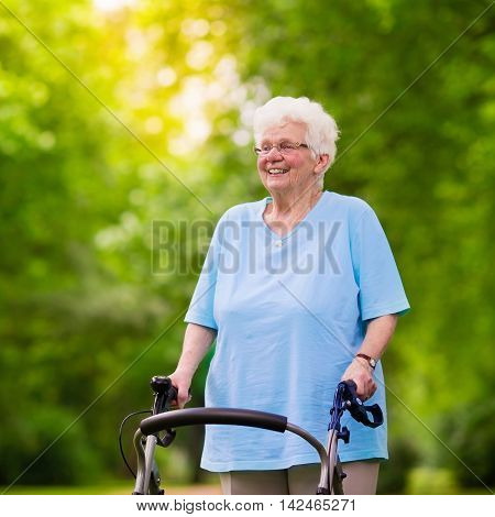 Happy senior handicapped lady with a walking disability enjoying a walk in a sunny park pushing her walker or wheel chair aid and support during retirement concept.