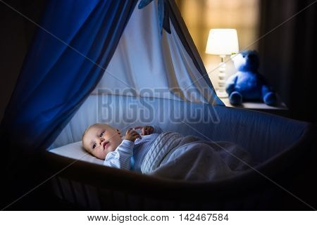 Adorable baby sleeping in blue bassinet with canopy at night. Little boy in pajamas taking a nap in dark room with crib lamp and toy bear. Bed time for kids. Bedroom and nursery interior.