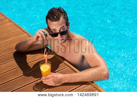 Magnetic glance. Pleasant handsome man sitting in the swimming pool and drinking cocktail while looking at you