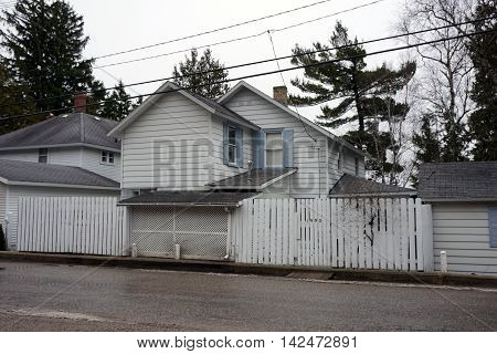 ROARING BROOK, MICHIGAN / UNITED STATES - DECEMBER 23, 2015: An elegant home behind a white picket fence on Pennsylvania Avenue in Roaring Brook.