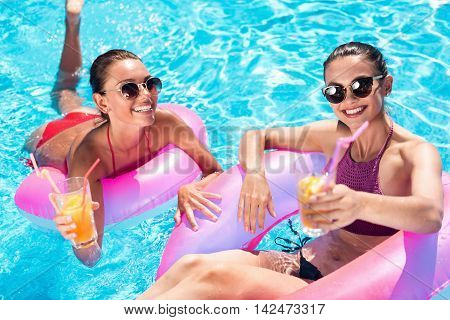 Join us. Delighted positive friend using inflatable rings and swimming in a pool while drinking cocktails