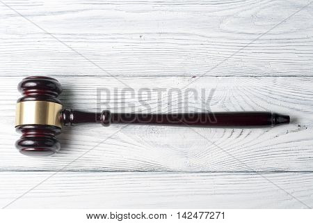 Law concept - wooden judges gavel on table in a courtroom or enforcement office