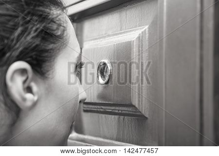 Girl looking through the peephole of her door. Toned photo.