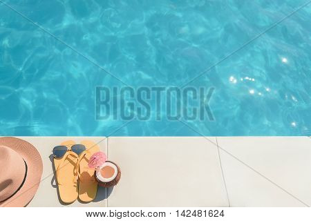 Close up of flip plops, coconut cocktail, sunglasses and hat near swimming pool