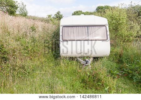 Forgotten Caravan Left Outside With Grass Growing Around It