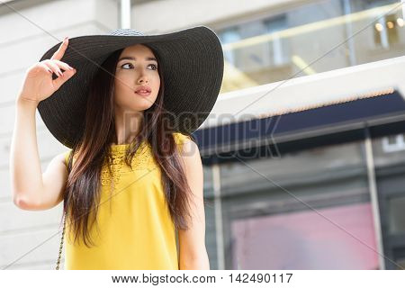 Fashionable young girl is standing on street in city. She is touching her sunhat with elegance and looking aside flirtingly