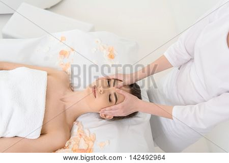 Top view of professional masseuse massaging female head at beauty salon. Young woman is lying and smiling with pleasure