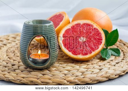 Aroma lamp with grapefruit essential oil on woven mat grapefruits on background horizontal