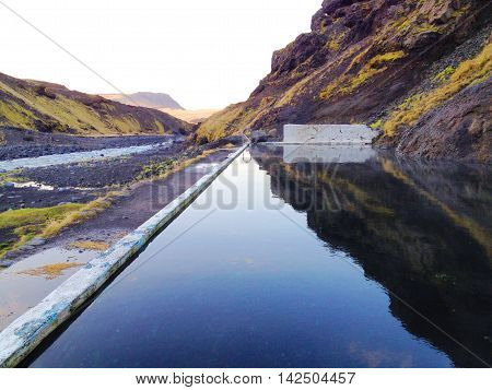Iceland nature hotspring / Natural hot spring in black pool among mountain valley in the south of Iceland