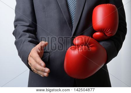 Businessman remove red boxing gloves to offer a handshake on white backgroundcompromise concept