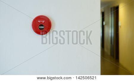 red fire alarm on wall beside walkway in condominium