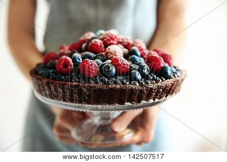 Woman holding chocolate tart with berries on light background