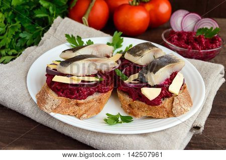 Meatless dietary sandwich: boiled beetroots purple onion salted herring and flakes of smoked cheese on a crispy baguette