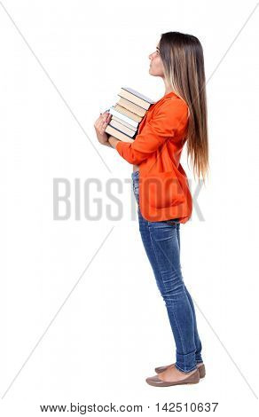 Girl carries a heavy pile of books. back view.  Rear view people collection.  backside view of person.  Isolated over white background. girl in a red jacket stands sideways with a stack of books and