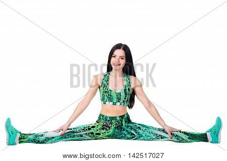 Young smiling brunette woman in green sportwear sitting on twine. Isolated in a studio on a white background