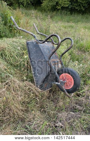 Vertical Shot Of An Upturned Wheelbarrow On A Compost Heap