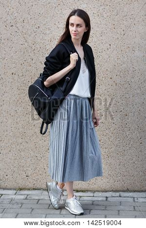 Young brunette woman in grey long skirt and black jacket stands in half-turn nearby wall outdoors