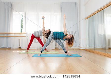 Two caucasian young women in yoga centre doing extended triangle pose, utthita trikonasana yoga asana