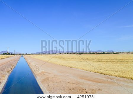 ROLL, ARIZONA, USA - MAY 25, 2015: An artificial irrigation canal in the Sonoran Desert with field to each side ot it that are ready for harvest.
