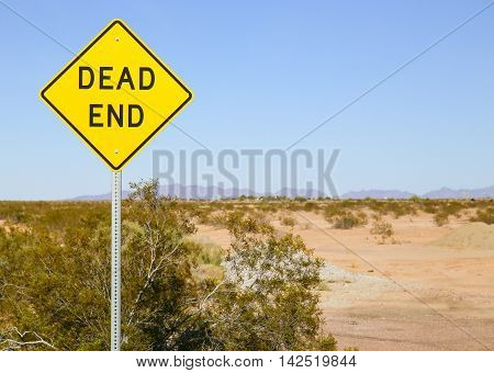 Dead End sign in the Sonoran desert Arizona USA with a mountain range in the back and shrubs growing on arid ground.