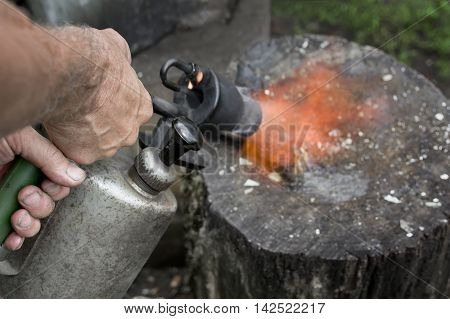 Male hand holding a petrol blowntorch pointed to a butcher block closeup with selective focus