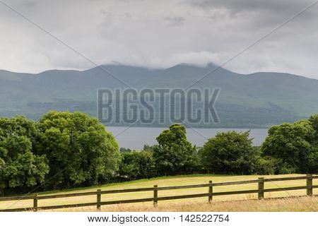 nature and landscape concept - view to lake or river, hills and farmland at connemara in ireland