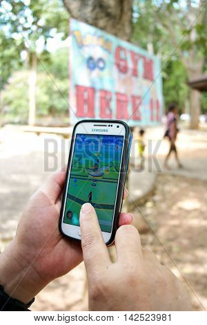 Korat Zoo, Thailand - AUGUST 13, 2016:Closeup of a women hand playing Pokemon Go on a smart phone. Korat Zoo is a Gym on map in Pokemon Go game.There is a famous zoo in Korat, Thailand.